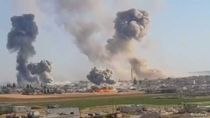 Plumes of smoke rise from a location, said to be Khan al Subul, Idlib province, Syria, following an airstrike, in this still image taken from a video uploaded May 28, 2019.