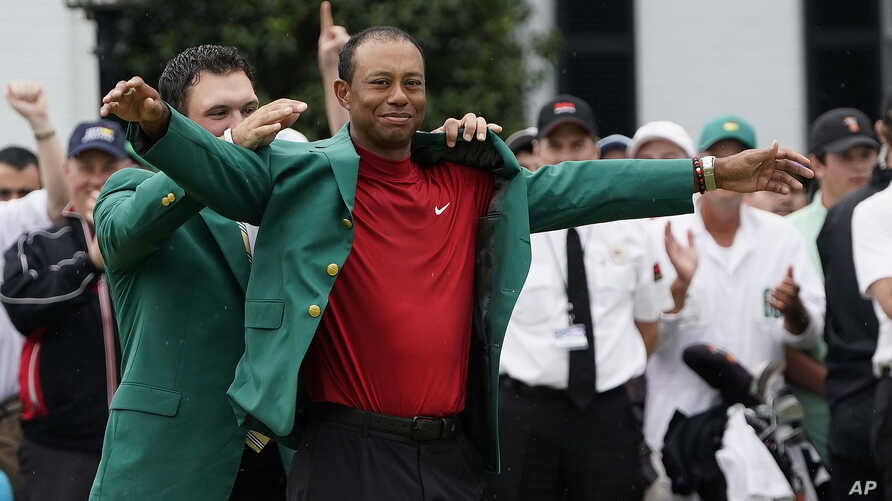 Patrick Reed helps Tiger Woods with his Masters green jacket after Woods won the Masters golf tournament, April 14, 2019, in Augusta, Ga.