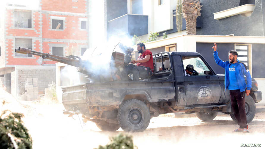A member of the Libyan internationally recognized government forces fires during a fight with eastern forces in Ain Zara, Tripoli, Libya, April 25, 2019.