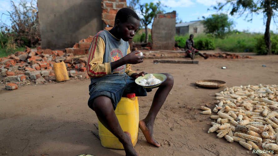 "Bernado Jofresse, 14, eats rice for breakfast as he sits beside his family's damaged house in the aftermath of Cyclone Idai, in the village of Cheia, which means ""Flood"" in Portuguese, near Beira, Mozambique, April 3, 2019."