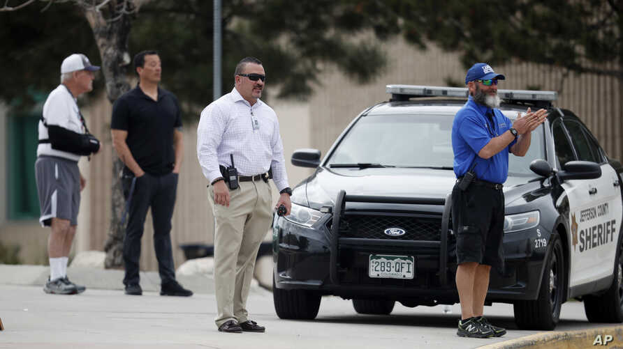 School police officers look on as students leave Columbine High School, April 16, 2019, in Littleton, Colo. Following a lockdown at Columbine High School and other Denver area schools, authorities say they are looking for a woman suspected of making ...