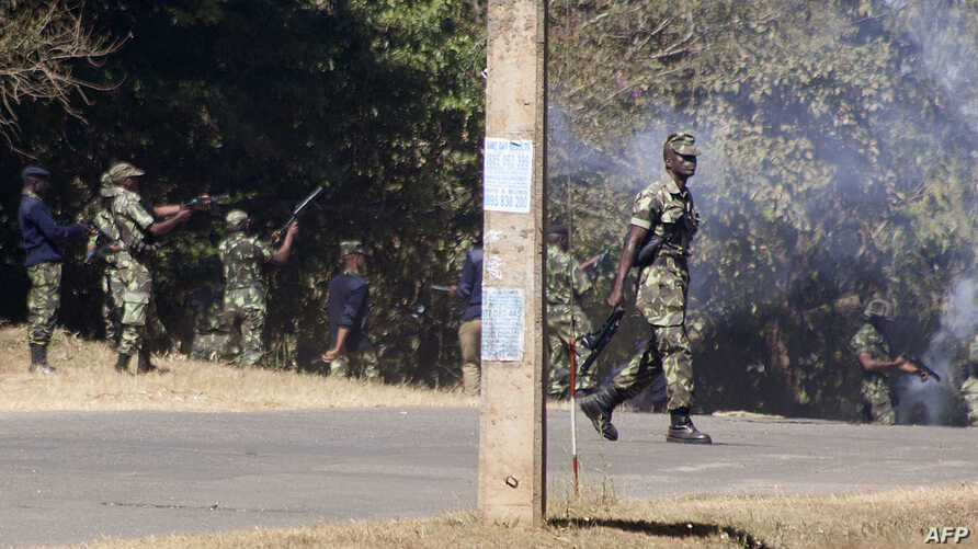 Armed Malawian policemen walk through a cloud of teargas as they disperse supporters of The Malawi Congress Party (MCP) in Lilongwe on June 6, 2019, as they attempt to prevent them from regrouping on the second day of their protest against recently Presid