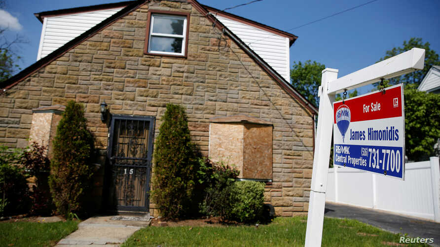 FILE - A 'for sale' is seen outside a single family house in Garden City, New York, US.