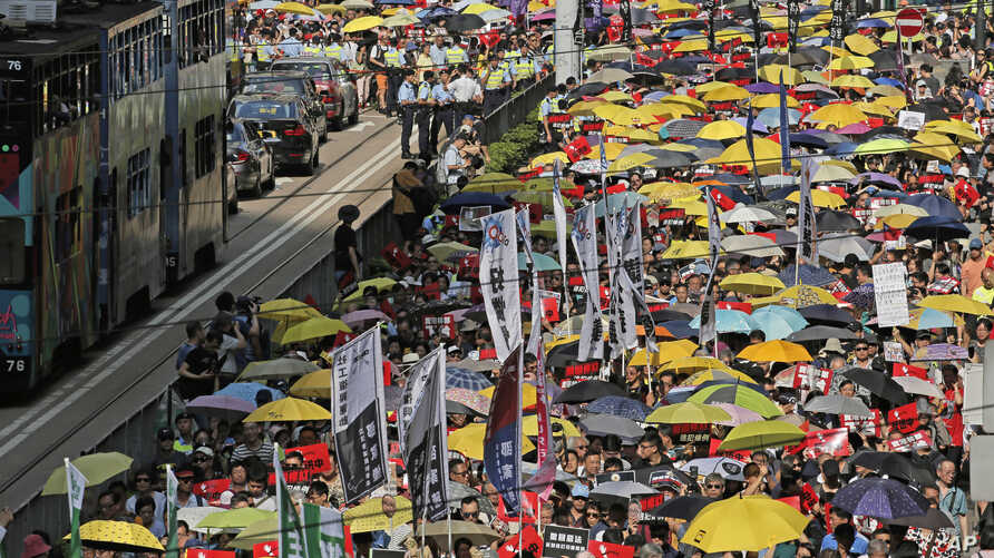 Thousands of protesters march along a downtown street against the extradition law in Hong Kong Sunday, April 28, 2019.