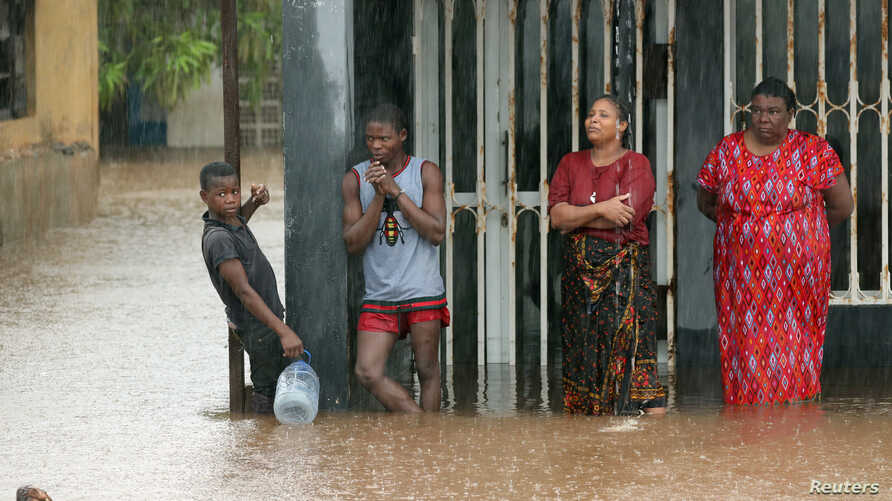 Residents stand outside a flooded house as rain falls in the aftermath of Cyclone Kenneth in Pemba, Mozambique, Apr. 28, 2019.