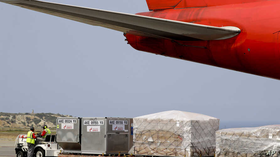 FILE - Workers unload medical supplies from a Chinese airplane at the Simon Bolivar International Airport in Maiquetia, near Caracas, Venezuela, March 29, 2019.