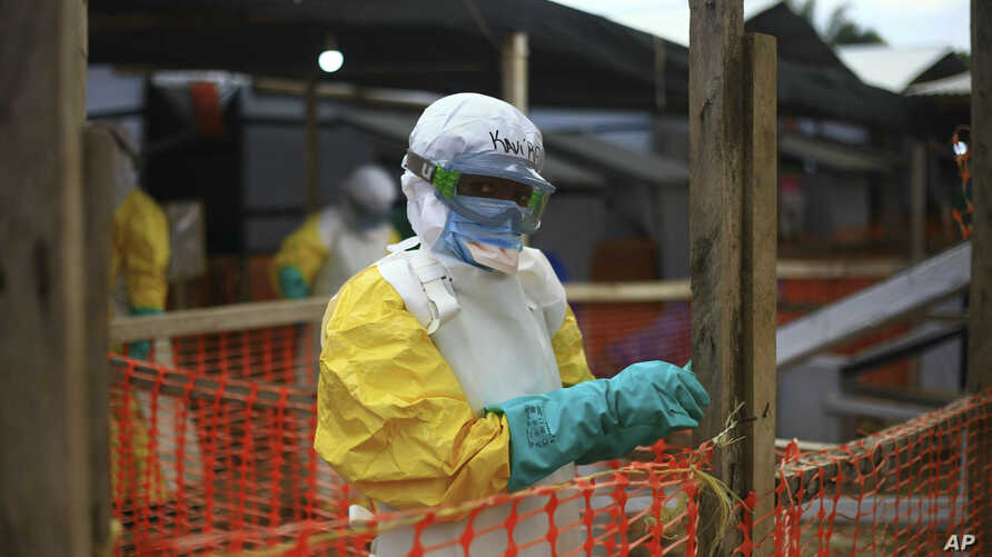 FILE - An Ebola health worker is seen at a treatment center in Beni, Eastern Congo, April, 16, 2019. The World Health Organization is warning it may not be possible to contain Ebola to the two affected provinces in eastern Congo if violent attacks on...