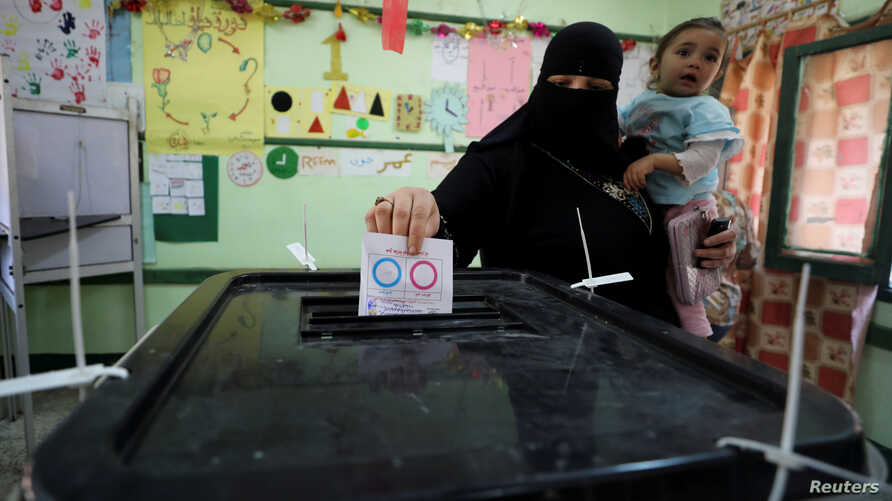 A woman casts her vote during the referendum on draft constitutional amendments, at a polling station in Cairo, Egypt, Apr. 20, 2019.