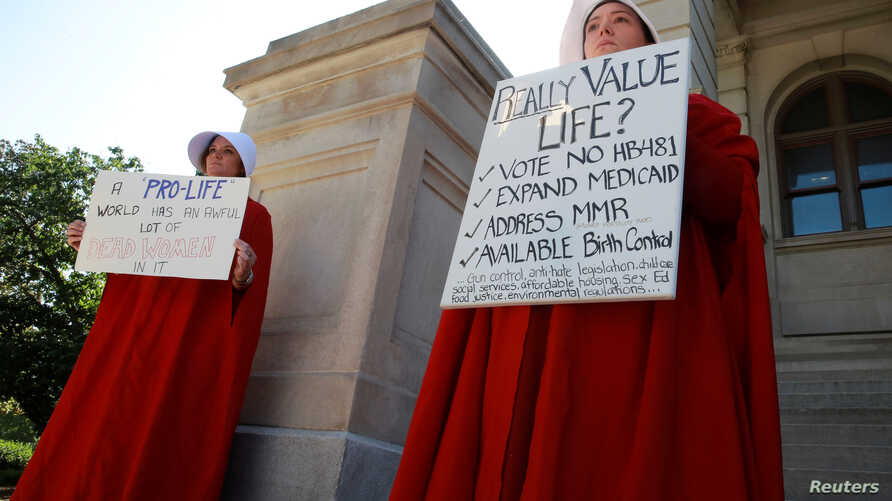 "April Houston and Lara Martin hold signs while dressed as Handmaids in protest of Georgia's anti-abortion ""heartbeat"" bill at the Georgia State Capitol in Atlanta, Georgia, U.S., May 7, 2019."