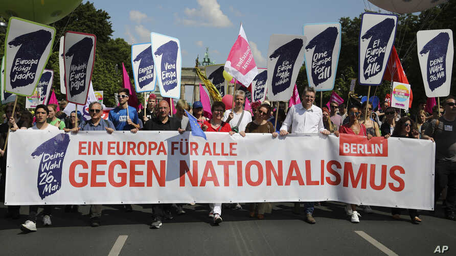 People walk with posters reading: 'Elect a Europe for all' and 'Your choice - May 26.' behind a banner reading: 'A Europe for all; against nationalism,' as they attend a demonstration in Berlin, Germany, May 19, 2019.