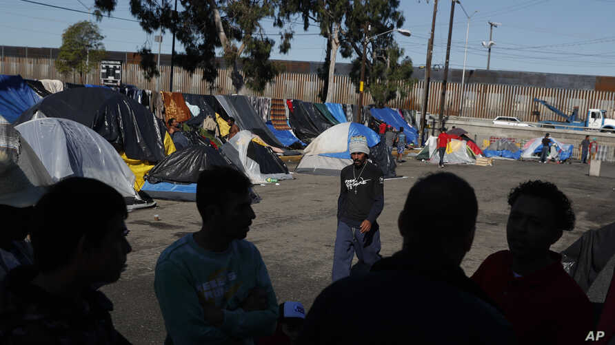 FILE - Men discuss rumors of other migrants who successfully snuck into the U.S. in a tent camp outside the closed Benito Juarez sports complex, in Tijuana, Mexico, Dec. 7, 2018.
