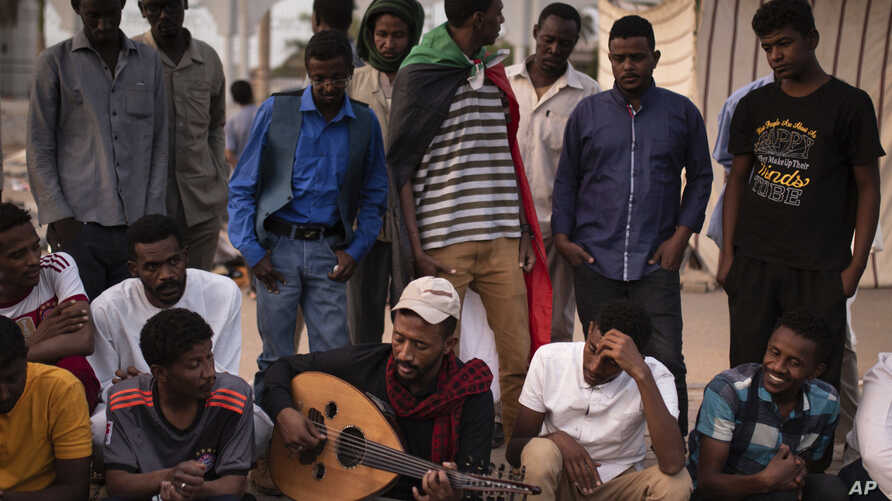 A protester plays music at the sit-in outside the military headquarters in Khartoum, Sudan, Saturday, April 20, 2019.