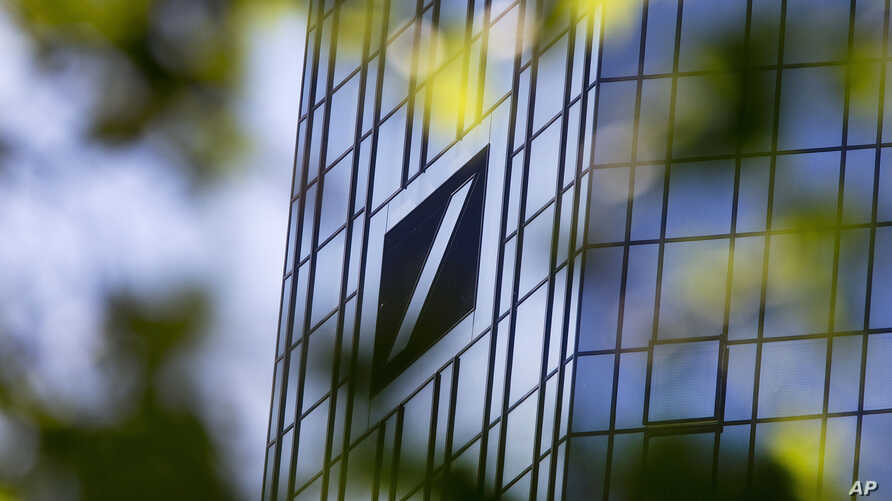 FILE - The headquarters of Deutsche Bank is seen through green leaves in Frankfurt, Germany, April 30, 2019.