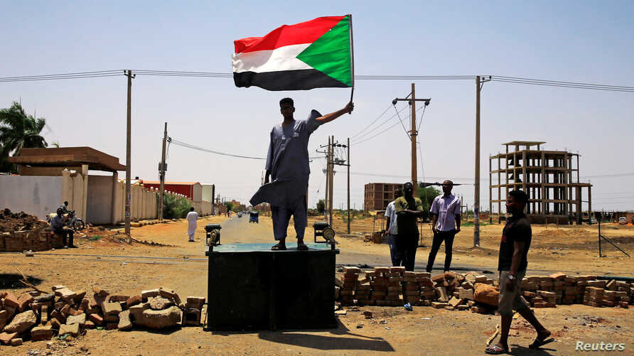 A Sudanese protester holds a national flag as he stands on a barricade along a street, demanding that the country's Transitional Military Council hand over power to civilians, in Khartoum, Sudan, June 5, 2019.