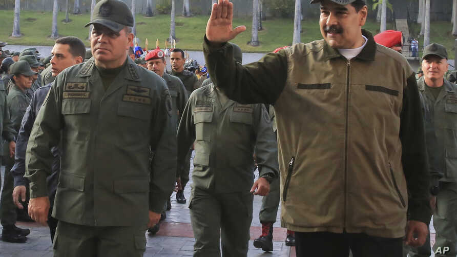 In this photo released by Miraflores Press Office, Venezuela's President Nicolas Maduro, right, accompanied by his Defense Minister Vladimir Padrino Lopez, waves upon his arrival to Fort Tiuna, in Caracas, Venezuela, May 2, 2019.