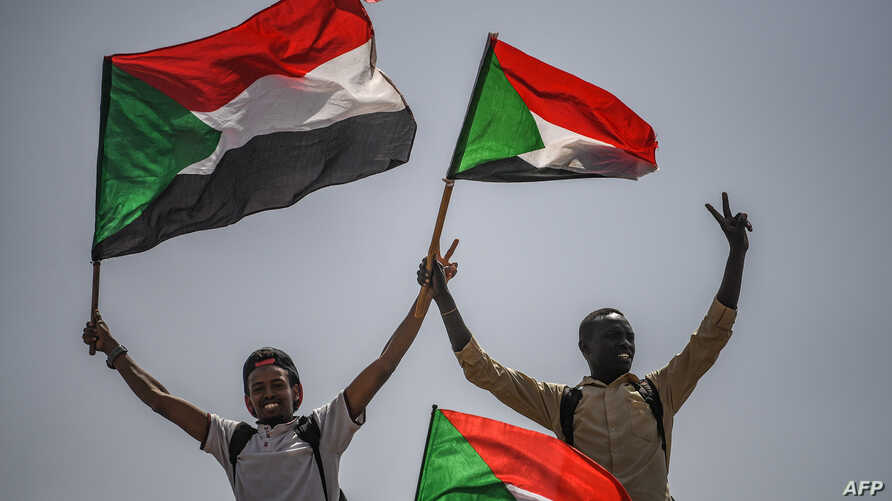 Sudanese protesters flash the victory sign and wave national flags during a rally outside the army headquarters in the capital Khartoum, April 19, 2019.