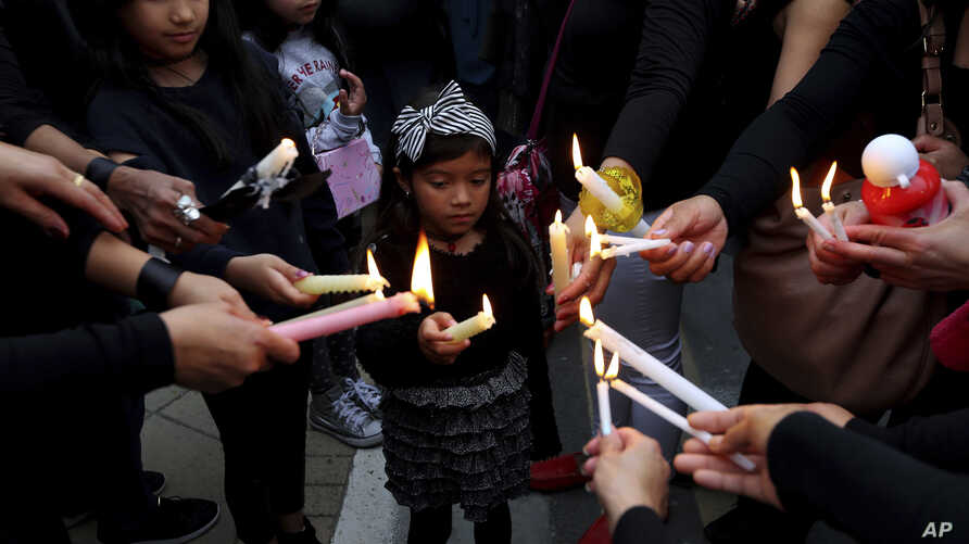 A girl among people during a vigil, outside of the presidential palace in Nicosia, Cyprus, April 26, 2019.
