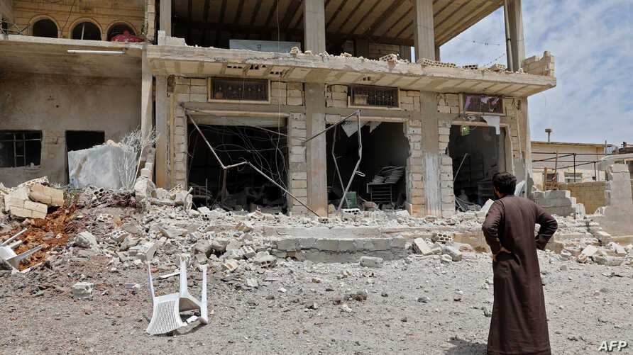 A man stares at a building damaged during reported shelling by government and allied forces, in the town of Hbeit in the southern countryside of the rebel-held Idlib province, May 3,2019.