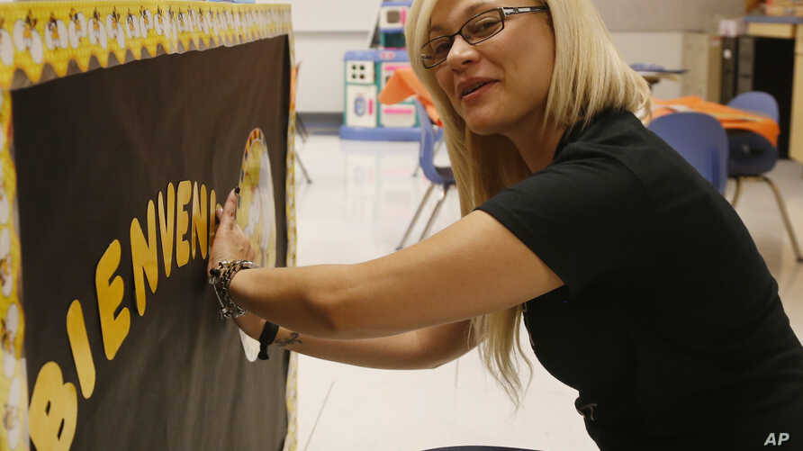 Odaliz Soto, of San Sebastian, Puerto Rico, makes a sign welcoming her kindergarden students at Parmelee Elementary School in Oklahoma City, July 31, 2015. Soso is one of 14 bilingual teachers recruited from Puerto Rico by the Oklahoma City School Di...