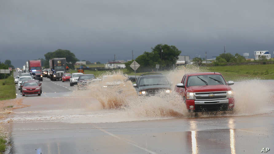Vehicles drive through floodwater on US Highway 66 following heavy rains, May 21, 2019, in El Reno, Okla.