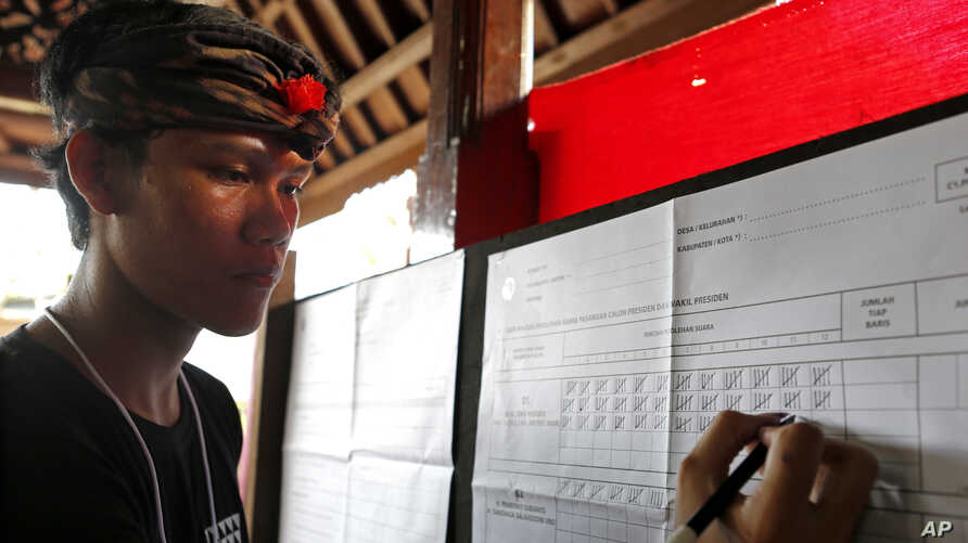 "An electoral worker checks a vote for presidential candidate Joko ""Jokowi"" Widodo during the vote counting at a polling station in Bali, Indonesia, April 17, 2019."