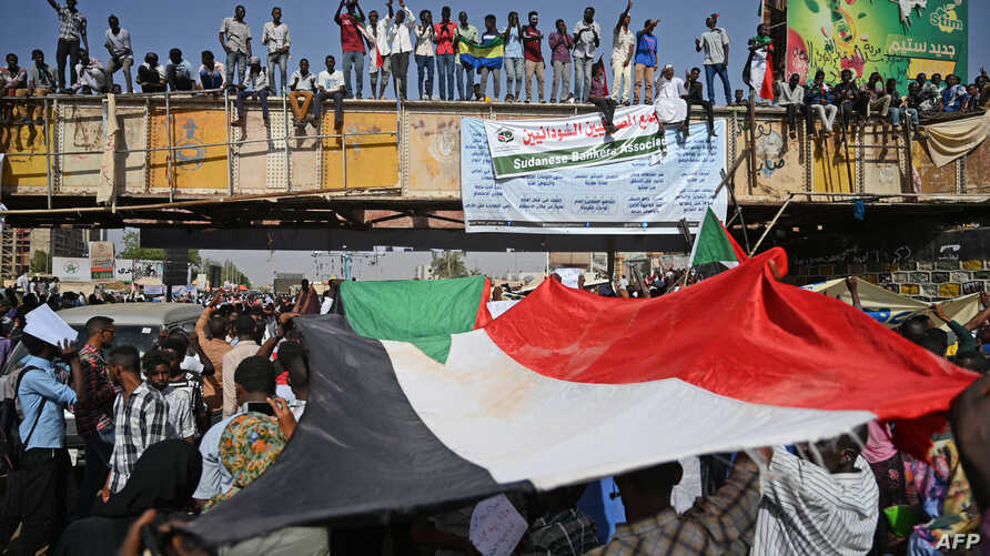"Sudanese protesters wave a national flag during a ""million-strong"" march outside the army headquarters in the capital Khartoum April 25, 2019."