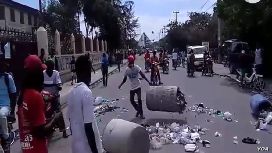 Protesters throw trash on street during a demonstration against President Jovenel Moise in Gonaïves, Haiti, June 14, 2019.