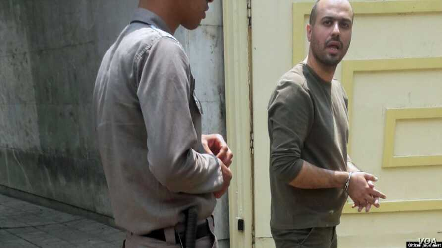 In this photo shared on social media, Iranian journalist Masoud Kazemi is seen handcuffed after being arrested in Tehran, May 22, 2019, for alleged security offenses.