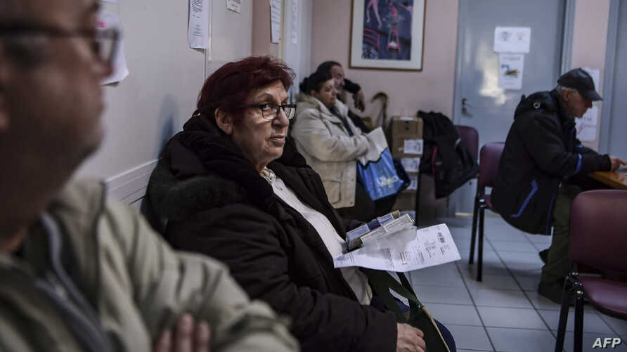 A woman waits to receive his medicines at the social pharmacy of Elliniko, Greece, Feb. 27, 2019.