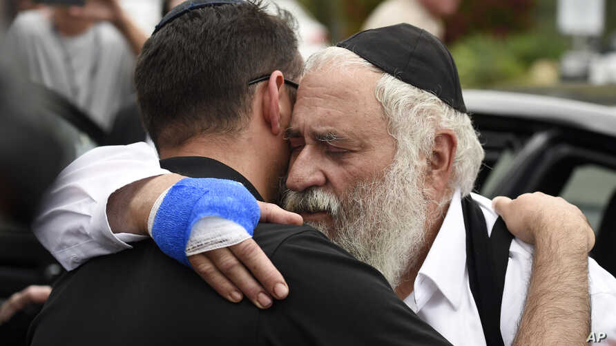 Rabbi Yisroel Goldstein, right, is hugged as he leaves a news conference at the Chabad of Poway synagogue, Sunday, April 28, 2019, in Poway, Calif.