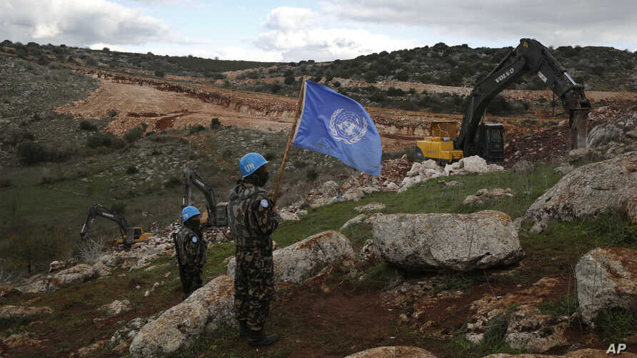 FILE - U.N. peacekeepers hold their flag as they observe Israeli excavators attempt to destroy tunnels built by Hezbollah, near the southern Lebanese-Israeli border village of Mays al-Jabal, Lebanon, Dec. 13, 2018.