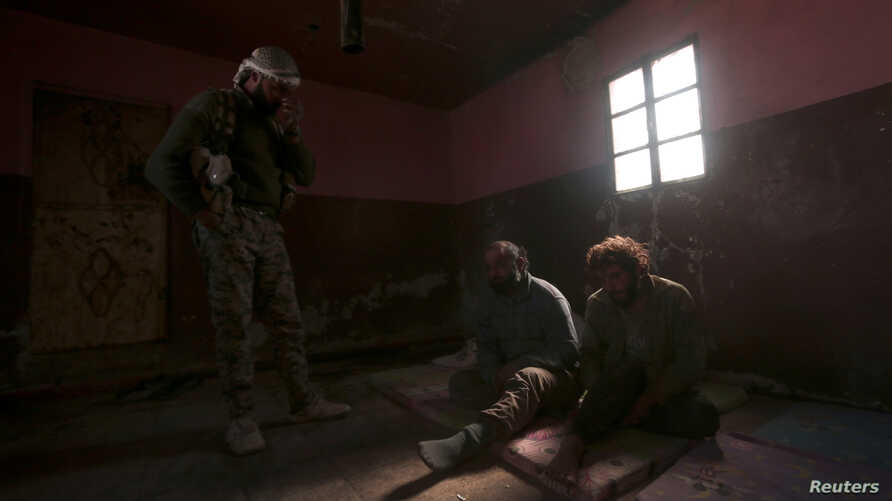FILE PHOTO: A Syrian Democratic Forces fighter stands near who he said were Islamic State fighters held prisoners, north of Raqqa, Syria March 8, 2017.