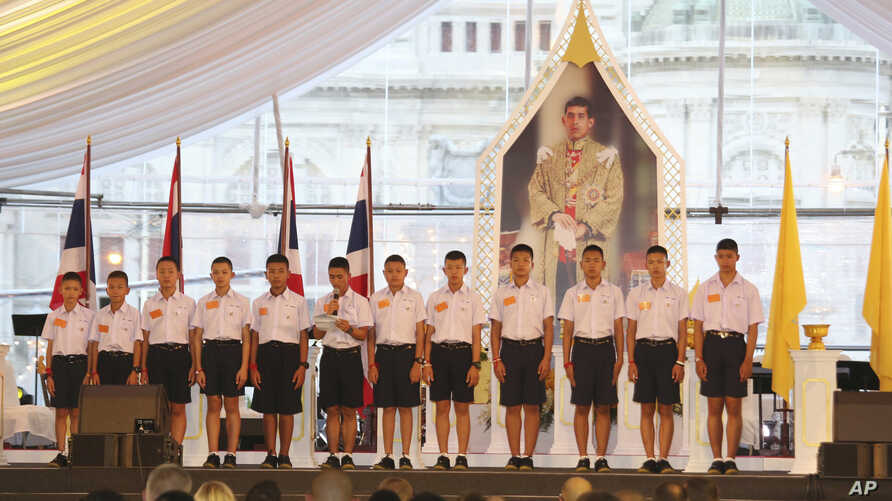 "FILE - Members of the Wild Boars, the soccer team that was rescued from a flooded cave, give thanks in front of Thailand King Maha Vajiralongkorn's image during an event titled ""United as One"" in Bangkok, Thailand, Sept. 6, 2018."