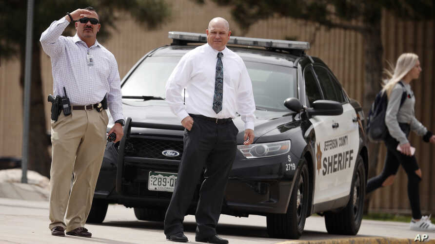 Columbine High School principal Scott Christy, right, joins an officer as students leave the school, April 16, 2019, in Littleton, Colo. Authorities say they are looking for a woman suspected of making threats.
