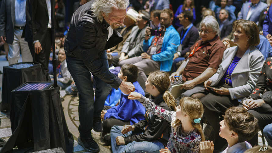 Virgin Galactic founder Richard Branson gives a fist bump to Sonia Thorp, 9, of Carlos Gilbert Elementary at the beginning of an event at the state Capitol, May 10, 2019, in Santa Fe, N.M.