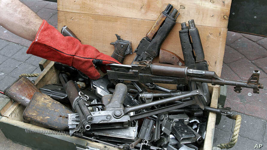 A Costa Rican poice officer packs destroyed hand-guns and assault rifles seized during police raids at the Cultural Plaza in San Jose, Costa Rica, Dec. 2, 2005.