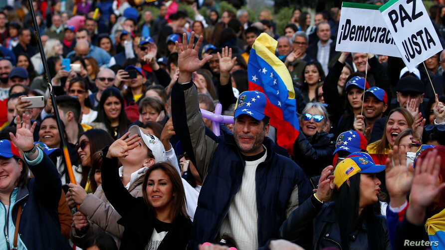 FILE - Protesters gather to call for humanitarian aid for Venezuela, in Madrid, Spain, Feb.  23, 2019.