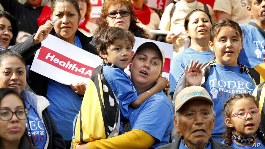 Oralia Sandoval, center, holds her son Benjamin, 6, as she participates in an Immigrants Day of Action rally in Sacramento, Calif., May 20, 2019.