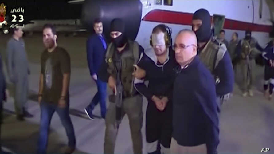 In this frame grab from Egyptian State Television, a blindfolded Hisham el-Ashmawi, a prominent Egyptian militant is escorted by Egyptian military officers and placed in a vehicle after being taken off a military plane at an airport in Cairo, Egypt, ...