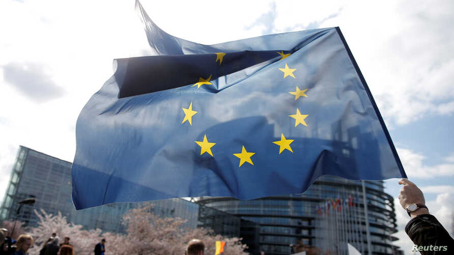 FILE - FILE - A demonstrator holds a European flag during a protest in front of the European Parliament in Strasbourg, France, March 26, 2019.