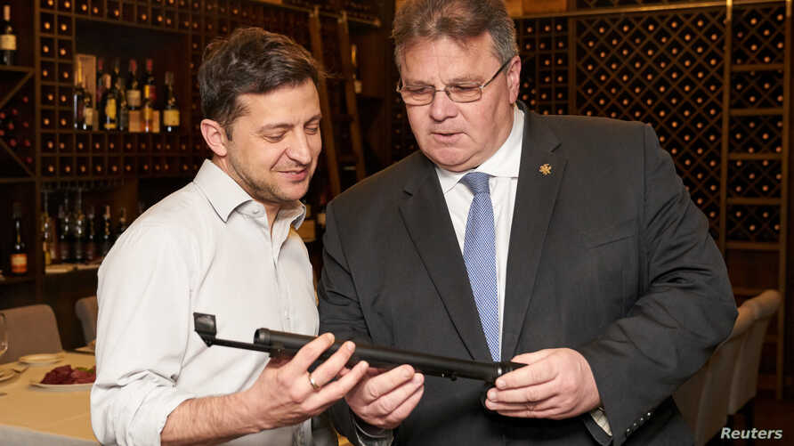 Ukraine's President-elect Volodymyr Zelenskiy, left, meets with Lithuania's Foreign Minister Linas Linkevicius in Kyiv, Ukraine, April 25, 2019.