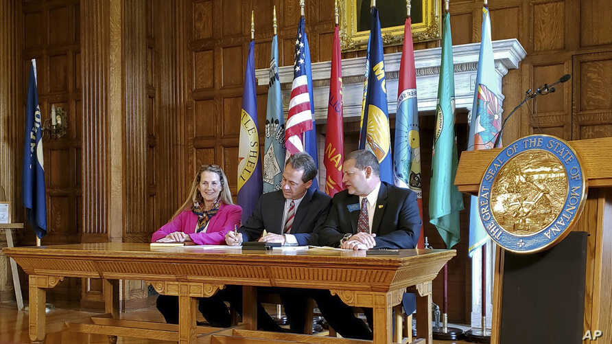 Democratic Rep. Mary Caferro, left, and Republican Rep. Ed Buttrey, right, look on as Democratic Gov. Steve Bullock signs a bill to continue Montana's Medicaid expansion program, May 9, 2019 in Helena, Mont.