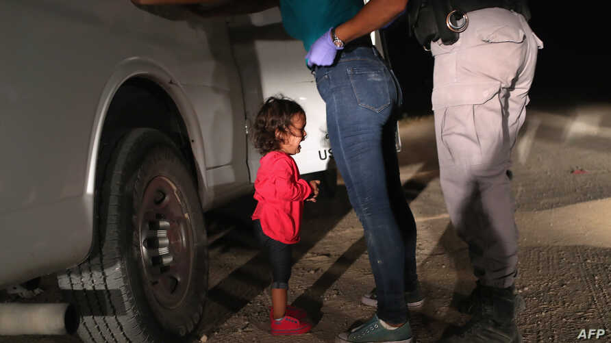 FILE - A 2-year-old Honduran asylum seeker cries as her mother is searched and detained near the U.S.-Mexico border in McAllen, Texas, June 12, 2018. Getty Images photographer John Moore won the 2019 World Press Photo of the Year award with this phot...
