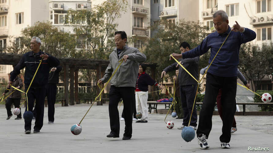 "Retirees practice ""Cola Ball"" with music, an invented community activity in central Beijing, China, Oct. 17, 2013."