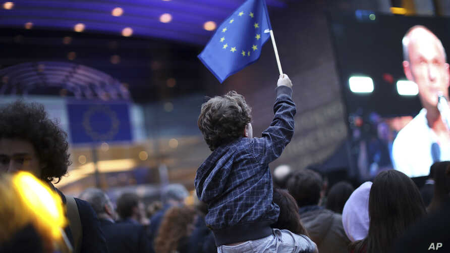 A young boy waves an EU flag as he watches a giant screen television outside the European Parliament in Brussels, Belgium, May 26, 2019.