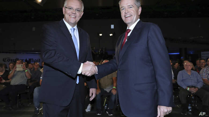 Australian Prime Minister Scott Morrison, left, and opposition leader Bill Shorten shake hands before the Sky News/Courier Mail People's Forum in Brisbane, May 3, 2019.