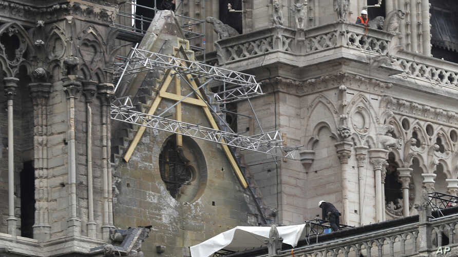Workers install tarps at Notre Dame cathedral in Paris, France, April 23, 2019.
