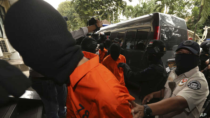Police anti-terror unit escort suspected militants before a press conference in Jakarta, May 17, 2019. Police say they have arrested suspected militants following a tipoff about a possible attack during the announcement of presidential election resul...