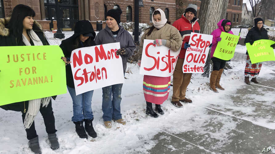 A group of demonstrators stand outside in below-freezing temperatures at the Cass County Courthouse in Fargo, N.D., Dec. 6, 2017, before a court appearance by a man accused in the killing of 22-year-old Savanna Greywind, of Fargo. The protesters were...
