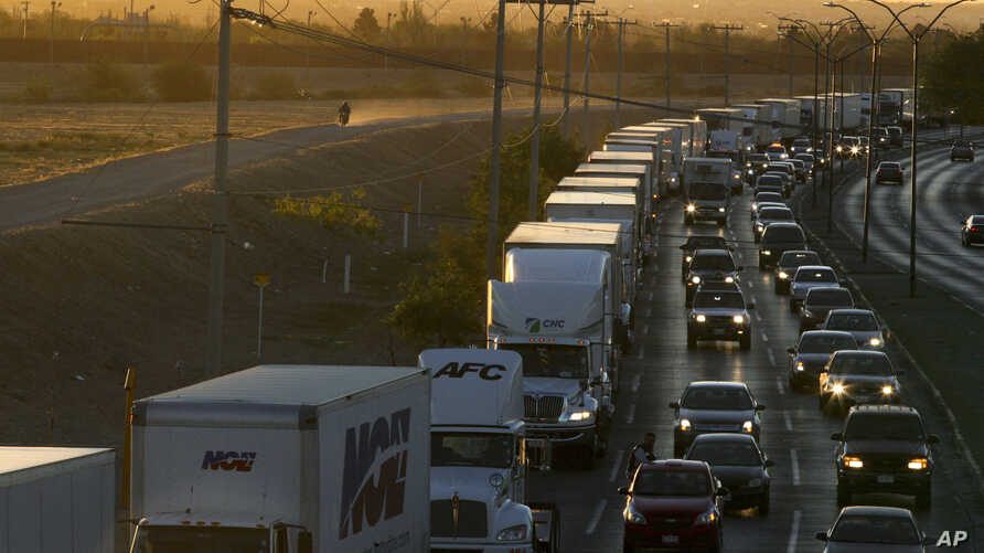 FILE- In this April 9, 2019, file photo, trucks wait to cross the border with the U.S. in Ciudad Juarez, Mexico.